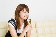 The woman who drinks wine. The young woman who drinks wine in a room Royalty Free Stock Images