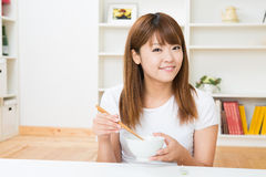 The woman who eats. The young woman who eats in a room Stock Image