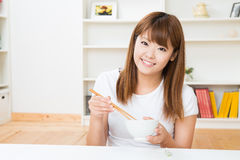 The woman who eats. The young woman who eats in a room Royalty Free Stock Photos