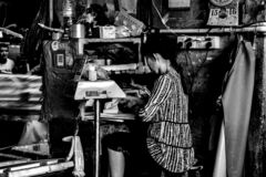 Woman who is in old roadside computing in Liwan District, Guangzhou,China royalty free stock photos