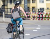 Girl cyclist lover of active lifestyle rides bicycle through crossroad on city street