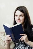 Woman, who reads book sitting on the sofa Stock Photos