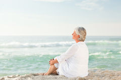 Woman who is sitting on the beach Royalty Free Stock Images