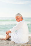 Woman who is sitting on the beach Stock Photo