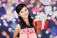 Smiling woman with gifts. The woman who smiles with presents Royalty Free Stock Images