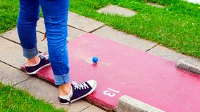 A woman teeing off at miniature golf. A woman who tee off at miniature golf. The ball is hit by the tee-off field through the obstacle structures and must pass Royalty Free Stock Photography