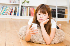 The woman who uses the smartphone. The Young woman who uses the smartphone in a room Royalty Free Stock Image