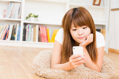 The woman who uses the smartphone. The Young woman who uses the smartphone in a room Royalty Free Stock Images