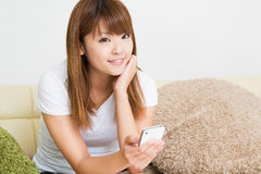 The woman who uses the smartphone. The Young woman who uses the smartphone in a room Royalty Free Stock Photo
