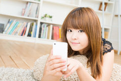 The woman who uses the smartphone. The Young woman who uses the smartphone in a room Royalty Free Stock Photos
