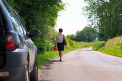 Woman whos car has run out of fuel. Photo of a woman who's vehicle has run out of petrol walking along a country lane with a spare fuel can in her hand Royalty Free Stock Images