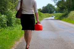 Woman whos vehicle has broken down. Photo of a woman who's vehicle has broken down walking along a country lane with a spare fuel can in her hand Royalty Free Stock Photo