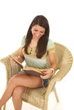 Woman in wicker chair reading smile look down Royalty Free Stock Photos