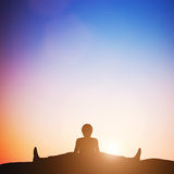 Woman in wide angle bend yoga pose meditating at sunset. Zen Royalty Free Stock Image