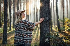Woman in wide-brimmed felt hat and authentic poncho standing in a foggy pine tree forest.  stock photography