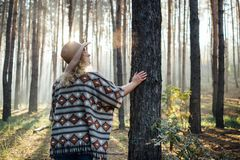 Woman in wide-brimmed felt hat and authentic poncho standing in a foggy pine tree forest. Woman in wide-brimmed felt hat and authentic poncho going along the stock image