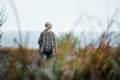 Woman in wide-brimmed felt hat and authentic poncho standing in high brown grass at foggy morning.  stock photo