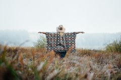 Woman in wide-brimmed felt hat and authentic poncho standing in high brown grass at foggy morning.  stock photos