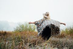 Woman in wide-brimmed felt hat and authentic poncho standing in high brown grass at foggy morning.  royalty free stock photos