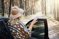 Woman in wide-brimmed felt hat and authentic poncho standing opening car door in the pine tree forest.  royalty free stock photo