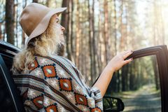 Woman in wide-brimmed felt hat and authentic poncho standing opening car door in the pine tree forest.  stock photography
