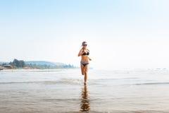 Woman on wide sandy beach Stock Photos