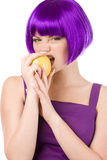 Woman in wig with yellow apple Stock Images