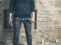 Woman wih hammer by wattle and daub wall. A young woman holding a hammer is standing by an old wattle and daub wall Stock Image