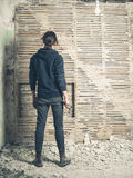 Woman wih hammer by wattle and daub wall. A young woman holding a hammer is standing by an old wattle and daub wall Royalty Free Stock Photography
