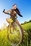 Woman wiht bike standing against the blue sky Royalty Free Stock Images