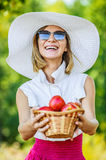 Woman wiht wicker basket holds red apples Stock Photo
