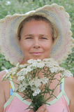 The woman and wild flowers. Stock Image