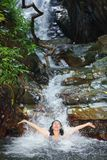Woman in wild waterfall Stock Photo