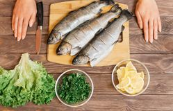Woman will cook fish on wooden table. stock images