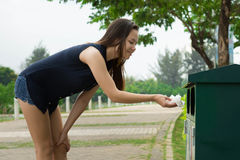 A woman willingly cleaning up litter at a park to help conserve and protect our environment. stock photography