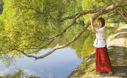Woman with willow tree and lake Royalty Free Stock Image