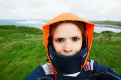 Woman with wind jacket standing against the elements. At the Cliffs of Moher, Ireland atlantic cloudy eyes face field girl grass green happy landscape meadow royalty free stock photo