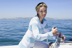 Woman winding rope pulley of boat rigging on deck of sailing boat out at sea, smiling, side view, portrait Stock Photos