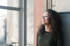 Woman at the window. Latin woman watching through her home window Stock Photo