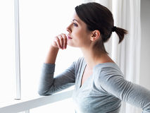 Woman by a window looking outside Stock Photo