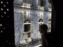 Woman at the window with sensual look in old alley, Stone Town royalty free stock images