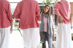 Woman window shopping, looking at three mannequins wearing pink tops and white skirts in clothes shop Stock Image