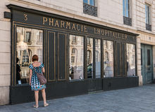 Woman window shops outside fashion store in historic pharmacy Stock Image