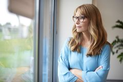 Woman by the window. Shot of a thinking middle aged woman looking out the window Stock Photography