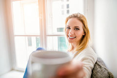 Woman on window sill holding a cup of coffee Royalty Free Stock Photo