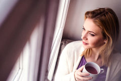 Woman on window sill holding a cup of tea Stock Photography