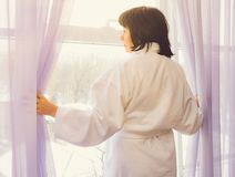Woman by the window sunlight Stock Photo