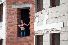 Woman in window of unfinished building Stock Images