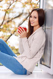 Woman on the windowsill with a cup of drink Royalty Free Stock Photo