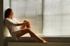 A woman on the windowsill at home Royalty Free Stock Images